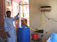 Halibet hospital technician holds AQUACHLOR generator (white cylinder) which converts brine in blue tub into sodium hypochlorite.